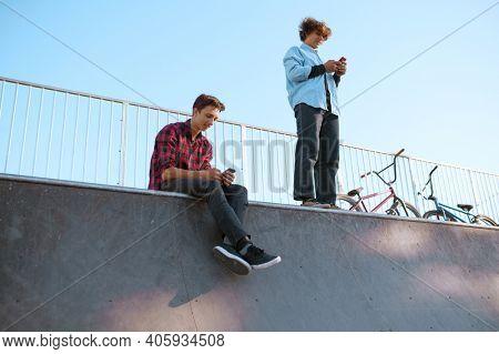Bmx bikers, teenagers leisures on ramp, skatepark