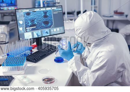 Virolog Examining Solution In Petry Dish In Modern Lab Sitting At His Workplace Dressed In Ppe Suit.