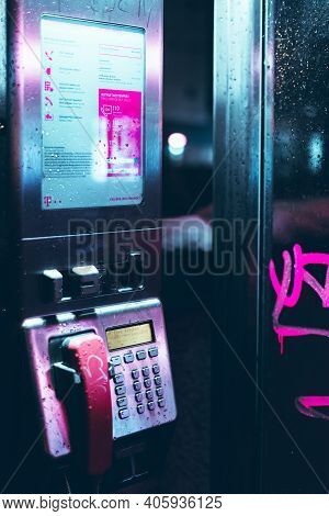 Augsburg, Bavaria, Germany - January 12th, 2021: Night Shot Of A Pink Telephone Booth Of Deutsche Te