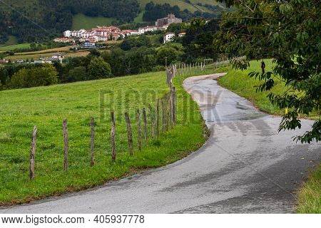 Winding Rural Country Road Goes Along Fence With Typical Rural Village And Church Of Basque Country,