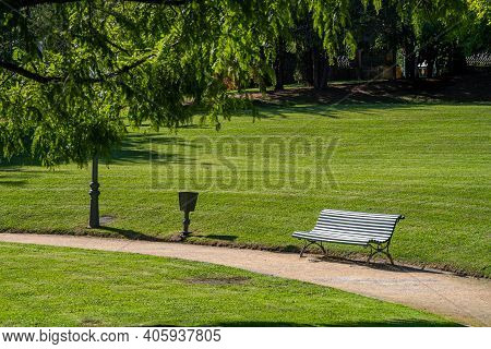 Wooden Slatted Bench In A Verdant Green Park With Neat Lawns And Woodland Trees At The Side Of A Wal