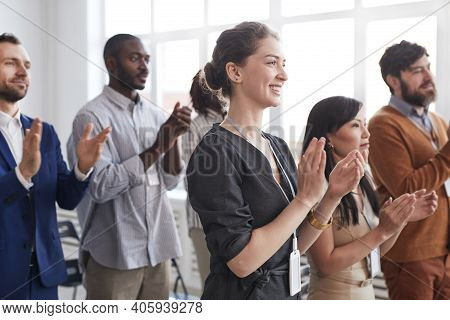 Side View At Multi-ethnic Group Of Business People Applauding Standing Up And Smiling In Audience At