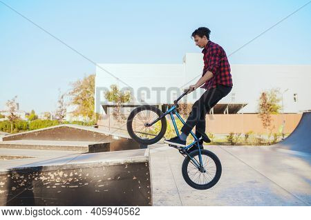 Young bmx biker doing trick, training in skatepark
