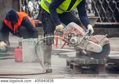 Worker Cutting The Curb With With Cut-off Saw. Road Works