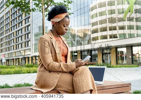 African businesswoman sitting on bench and typing a message on her mobile phone outdoors in the city
