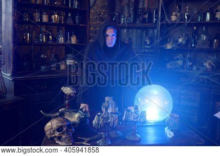 Male exorcist in hood near the magic crystal ball