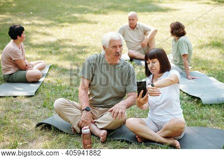 Senior couple sitting on the grass and discussing sports tracker on their gadgets during sports training in the park