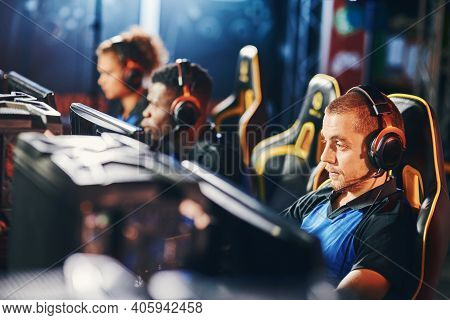 Focused On Game. Male Cybersport Gamer Wearing Headphones Playing Online Video Games, Participating