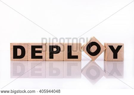 Deploy Word, Text Written On Wooden Cubes On A White Background With Reflection.