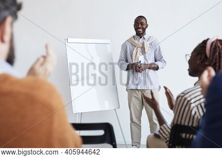 Full Length Portrait Of African-american Business Coach Talking To Audience At Conference Or Educati