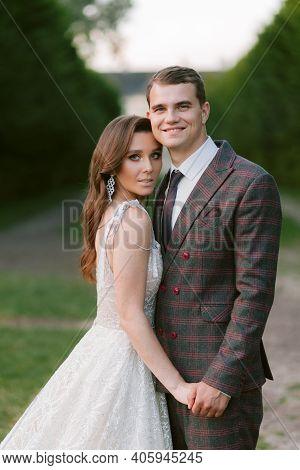 The Portrait Of Stunning Bride And Smiling Groom. Happy Newlyweds. Wedding Couple. Wedding Photo
