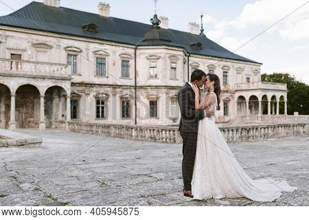Bride And Groom Kissing Each Other In The Background Of The Old Palace