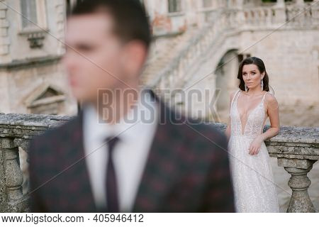 Portrait Of The Beautiful Bride With Blurred Groom In The Foreground