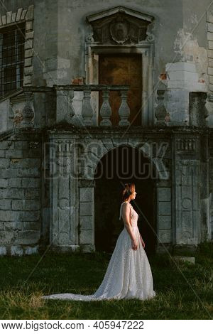 Stunning Bride Standing In Front Of Old Destroyed Palace. Beautiful Bride In Profile. Wedding Photo