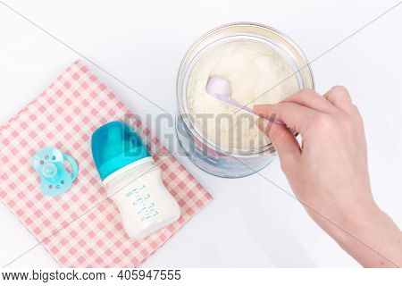 Woman's Hand Grabbing A Scoop Of Powdered Baby Milk. Baby Milk Formula And Baby Bottles