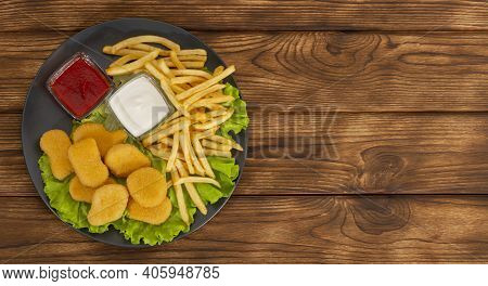 Delicious Crispy Fried Chicken Nuggets And French Fries Close-up With Sauce On The Plate. A Bunch Of