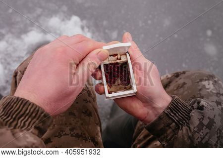 Man Holding The Box With Fishing Bait In His Hand. Winter Fishing On Ice. Red Bait. Putting Bait On