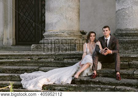 The Stunning Bride And Groom Sitting On The Stairs Of The Old Building With Columns. Wedding Couple.