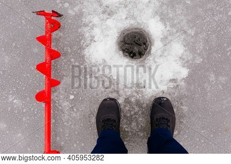 View Of The Ice Hole, Man Boots And Red Ice Screw. Winter Fishing On The Lake. Ice Fishing Concept