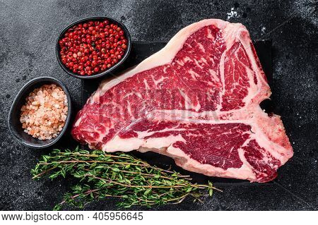 Dry-aged Raw T-bone Or Porterhouse Beef Meat Steak With Herbs And Salt. Black Background. Top View
