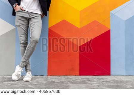 Crop Anonymous Male In Trendy Gray Skinny Jeans And White Sneakers Holding Hand In Pocket While Lean