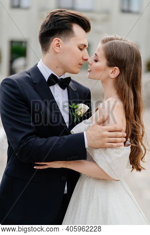 Beautiful, Gentle And Happy Bride And Groom Hugging And Kissing