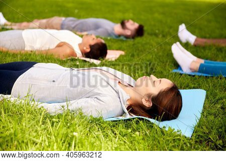 fitness, sport and healthy lifestyle concept - group of people doing yoga corpse pose or savasana at summer park