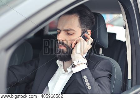 young man drives a car while telephoning