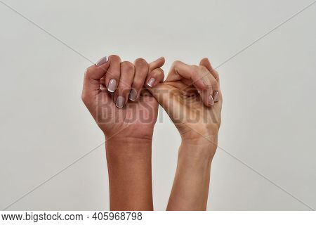 Close Up Shot Of Pinky Swear. Promise Hand Gesture Isolated Over Light Background. Horizontal Shot