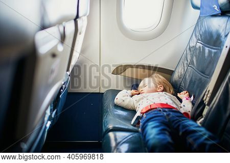 Adorable Little Toddler Girl Traveling By Plane. Small Child Lying On A Seat And Sleeping During The