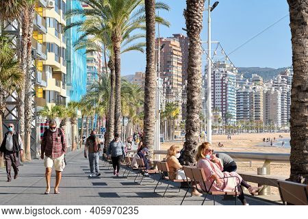 Benidorm, Spain - December 24, 2020: People Strolling Along Seaside Promenade In The Touristic City