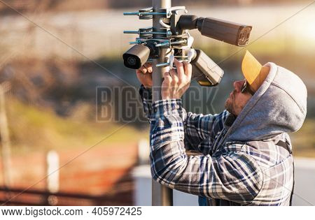 Caucasian Cctv Technician In His 40s Installing Ip Cameras On A Pole During Cold Weather. Modern Dig