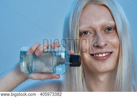 Happy Young Caucasian Man With Long Blond Hair Holding Bottle With Mouthwash Liquid While Standing O