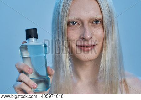 Smiling Young Caucasian Man With Long Blond Hair Holding Bottle With Mouthwash Liquid While Standing
