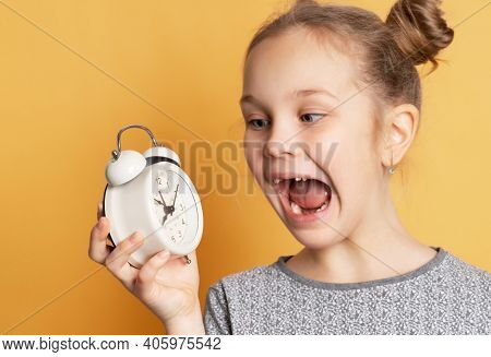 Close Up Of Shocked Schoolgirl Holding Alarm Clock And Shouting While Standing On Yellow Background.