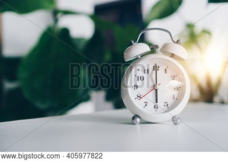 Selective Focus Of Alarm Clock Show 6 O'clock Or 6 A.m. On Table With Nature Bokeh Background. Time