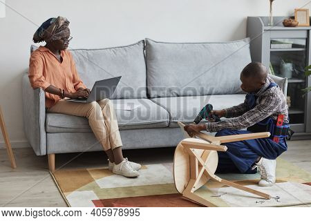 Full Length Portrait Of African-american Handyman Helping Young Woman Repair Or Assemble Furniture,