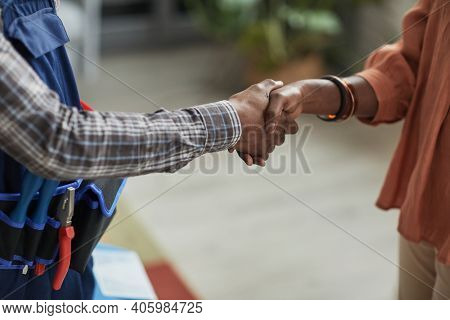 Close Up Of Unrecognizable African-american Woman Shaking Hands With Handyman Standing In Home Inter