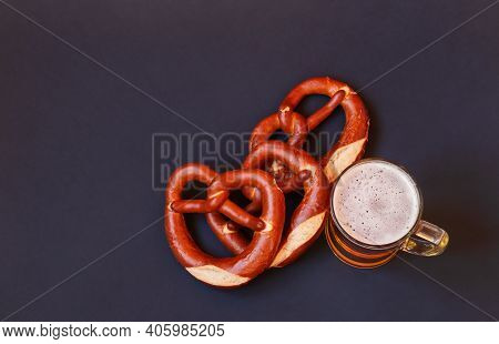 Beer Mug And Soft Pretzels On Dark Background.  Top View, Copy Space.
