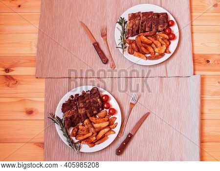 Baked Pork Ribs On Plates With Roasted Potatoes, Rosemary And Cherry Tomatoes  On Wooden Table. Top
