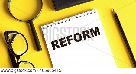 Notepad With The Text Reform On A Yellow Background With Glasses, A Magnifying Glass And A Pencil. B
