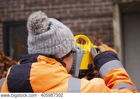 Female Land Surveyor Operating A Digital Precision Measurement Level To Establish Or Verify Or Measu