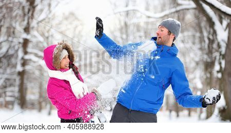 Winter outdoor fun happy interracial couple playing in snow throwing snowballs during snowball fight in park outside. Laughing asian woman with caucasian young man in winter coats.