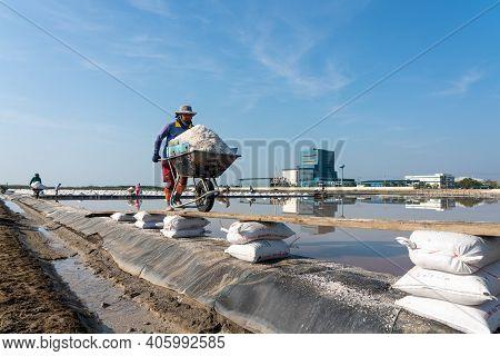 Samutsongkram, Thailand - March 10, 2019: Salt Farmer Is Puching Wheelbarrow Full Of Salt On Salt Fa