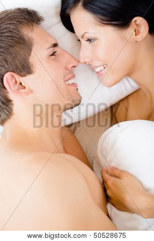 Close up of couple lying in bed close to each other, top view. Concept of love and affection