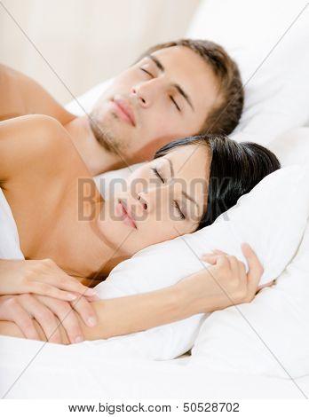 Couple sleeping in bedroom under white eiderdown