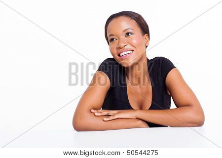 happy african woman sitting at a desk fantasizing isolated on white