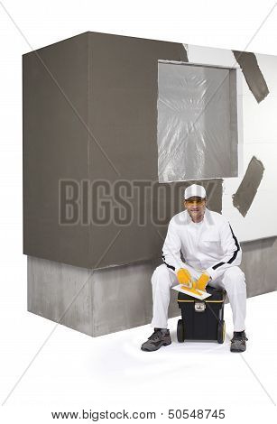 Worker Sitting On A Box Of Tools