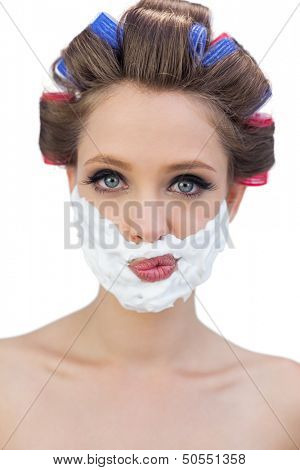 Thoughtful model in hair curlers posing with shaving foam on white background