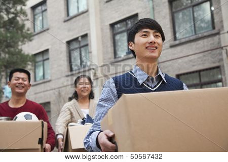 Family moving boxes into a dormitory at college
